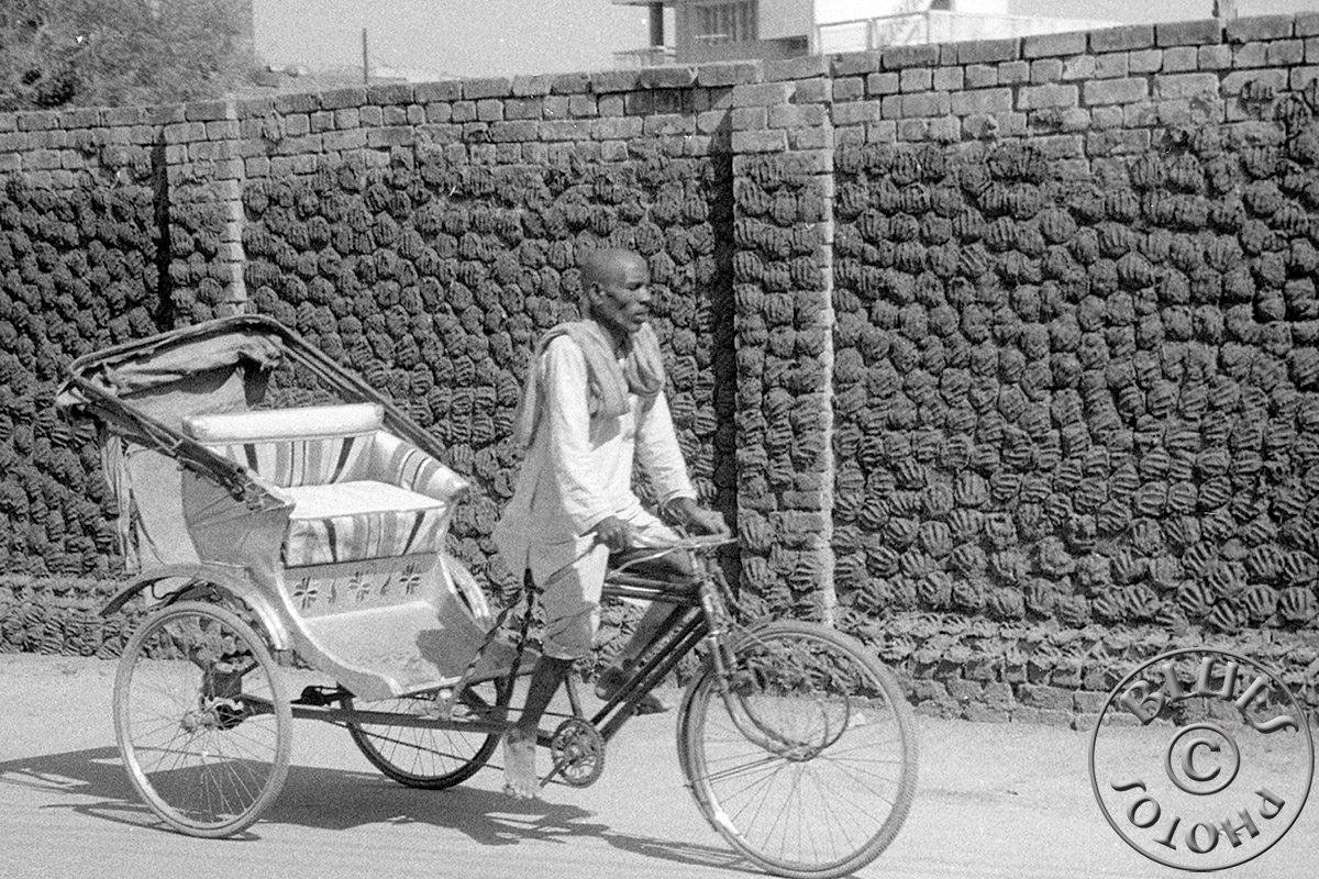 Bénarès, un rickshaw ... galettes de bouse séchaBénarès, un rickshaw ... galettes de bouse séchant sur le mur (combustible de chauffe)nts suz le mur (combustible de chauffe)